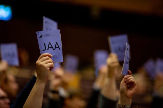 Käsiäänestyksessä ylös nostettuja äänestyslippuja / Voting tickets raised in peoples hands